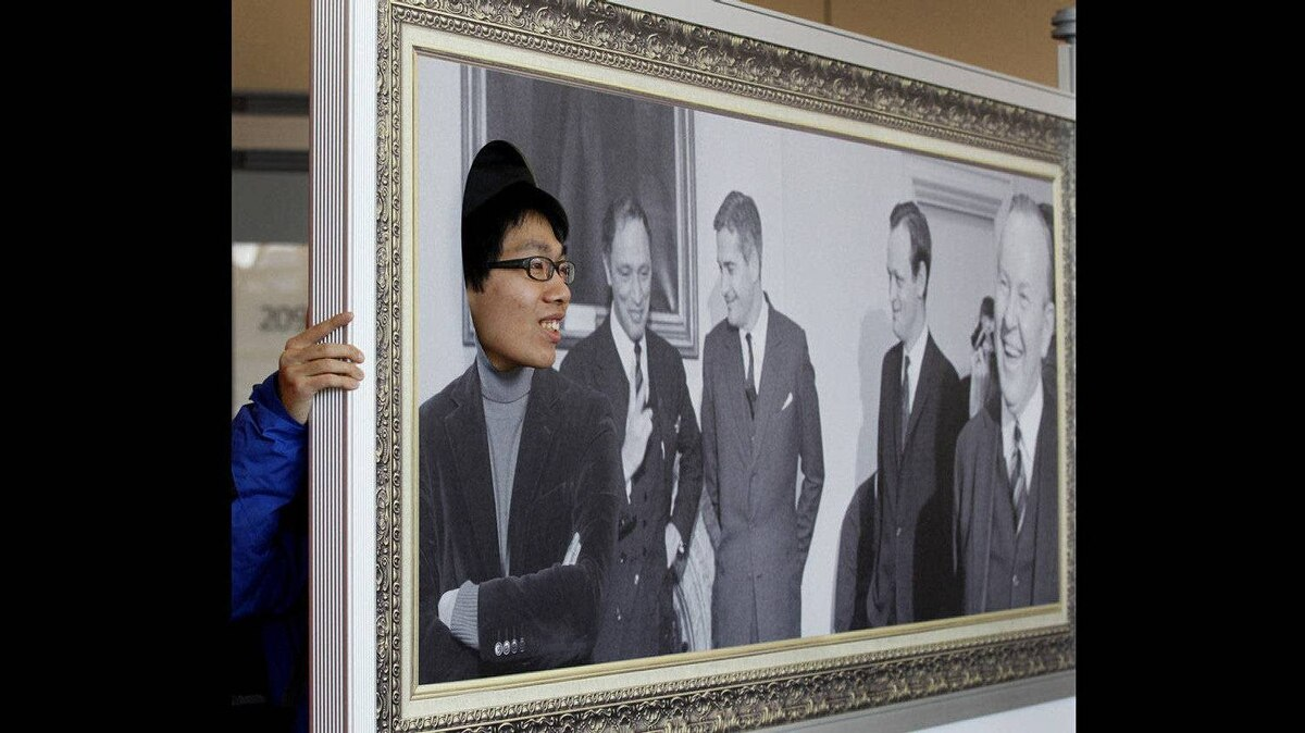 A visiting political science student from Hong Kong, Ken Li, 22, has his photo taken in the portrait frame with some famous Liberals.