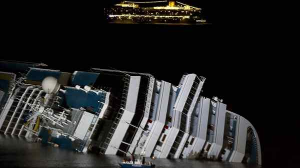 The cruise ship Costa Serena passes offshore as its sister ship, Costa Concordia, lies on its side off the tiny Tuscan island of Giglio, Italy, on Wednesday.