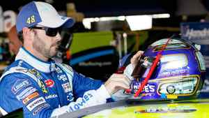 Jimmie Johnson reaches for his helmet in the garage during practice for the NASCAR Sprint Cup Series Good Sam Club 500 at Talladega Superspeedway on October 21, 2011 in Talladega, Alabama.