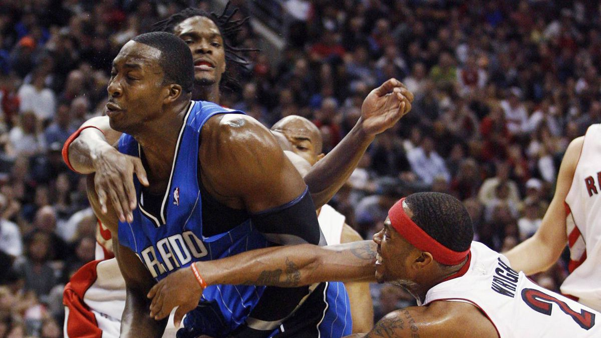 Orlando Magic centre Dwight Howard, left, is double teamed by Toronto Raptors forwards Chris Bosh and Antoine Wright during the second half of their NBA basketball game in Toronto November 1, 2009. Bosh drew a foul on the play.