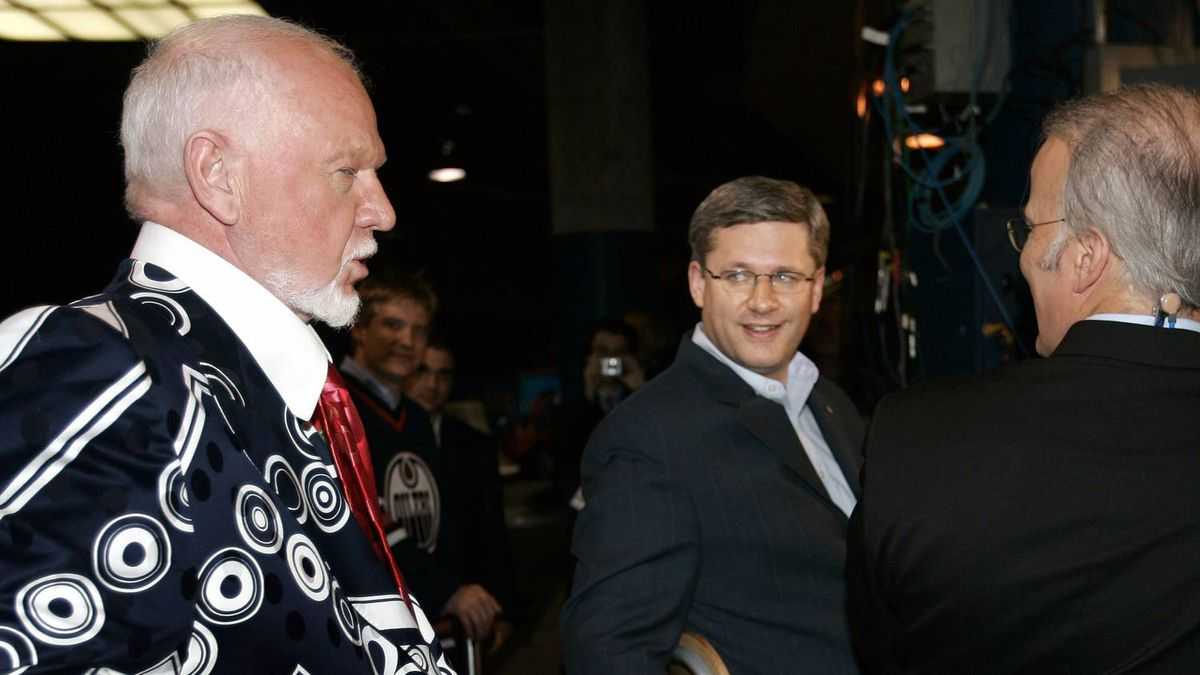 Prime Minister of Canada Stephen Harper (C) talks with television personality Don Cherry (L) before an interview at Game 6 in their NHL Stanley Cup ice hockey finals between Carolina Hurricanes' and Edmonton Oilers' in Edmonton, Alberta June 17, 2006