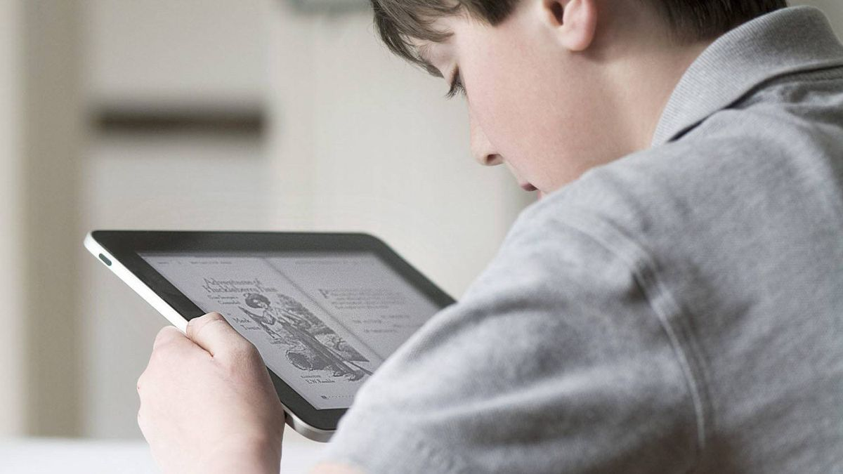 A boy is shown reading a school assignment on an iPad.