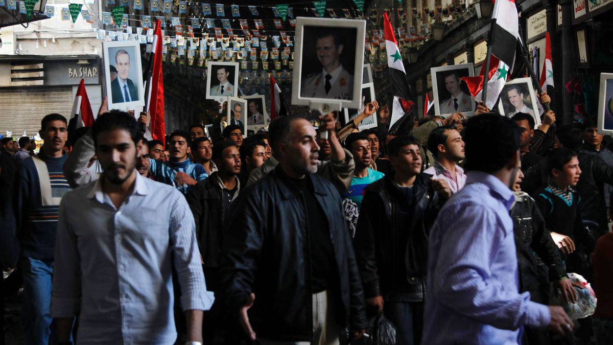 Syrian pro-government protesters hold pictures of Syrian President Bashar al-Assad and his late father and predecessor Hafez al-Assad, left, during a pro-regime rally at Al-Hamidiyah market in Damascus on March 18, 2011.
