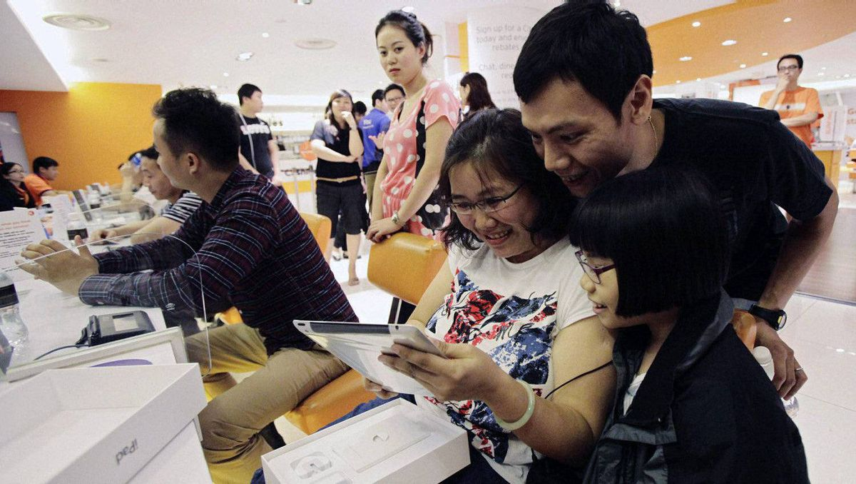 Zhuo Hanling with his wife Seah Swee Kheng and their daughter look at one of their third generation iPads after being first in line to purchase the tablet computer in Singapore March 16, 2012. The new iPad is going on sale on Friday in 10 countries, including the United States, Canada, Singapore, France and Britain.