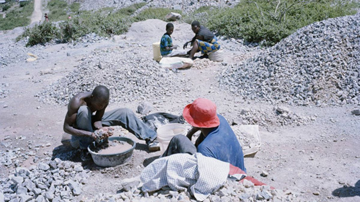 Artisan miners search through waste rock for gold deposits on the edge of North Mara Mine, Tanzania.