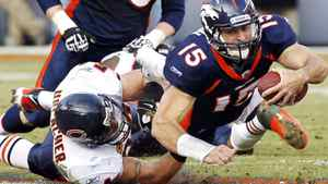 Denver Broncos quarterback Tim Tebow is tackled by Chicago Bears linebacker Brian Urlacher during their NFL football game in Denver December 11, 2011. The Broncos won 13-10 in overtime. REUTERS/Rick Wilking