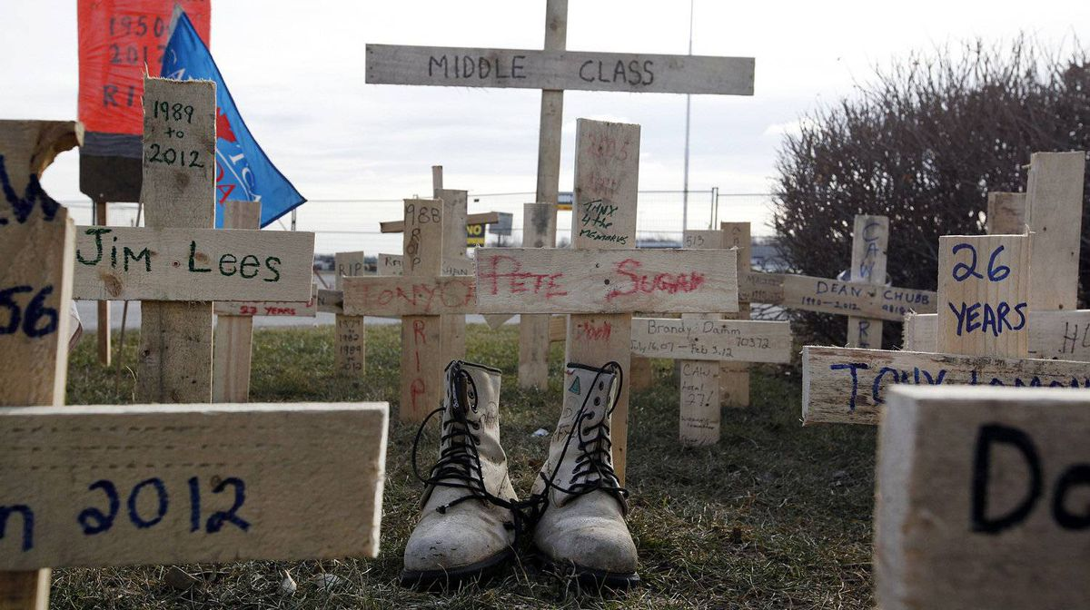 Electro-Motive Canada employees put up a graveyard of crosses and workers' boots outside the subsidiary of Caterpillar in London on Feb. 8, 2012.