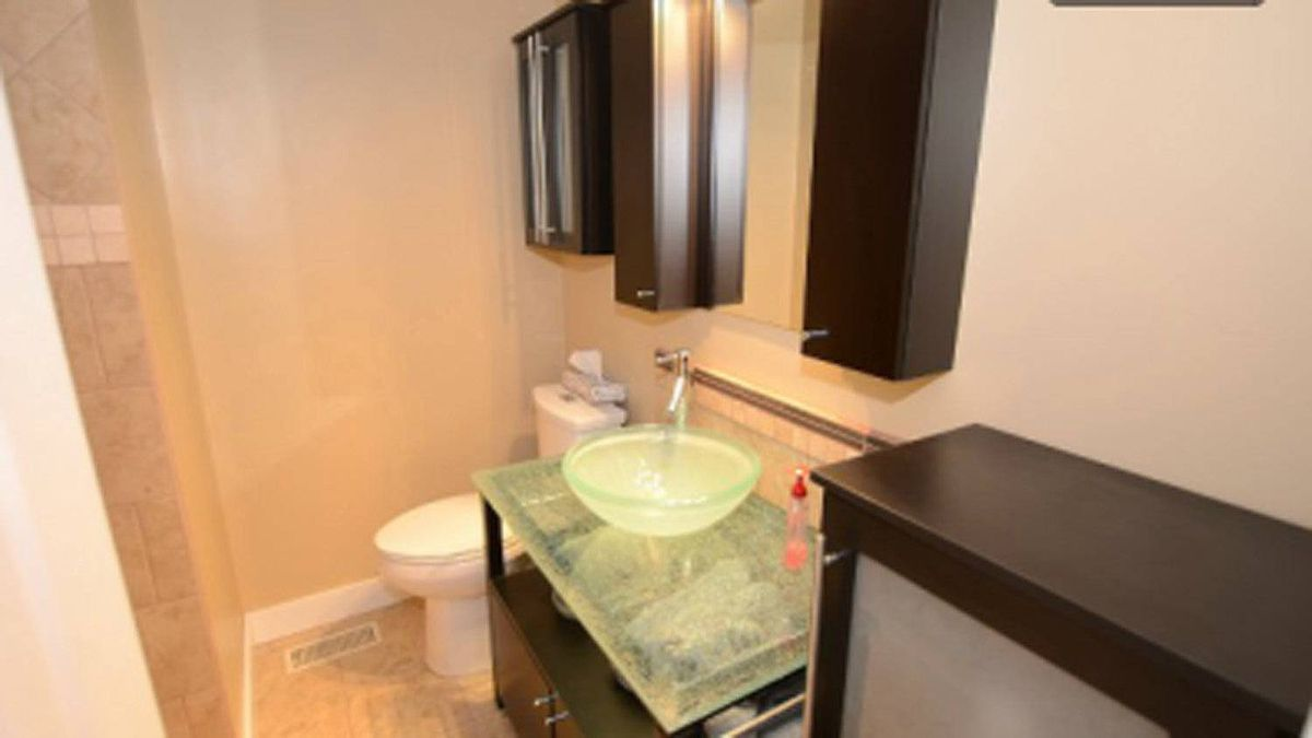 An updated bathroom features a modern vanity and vessel sink as well as an oversized shower.