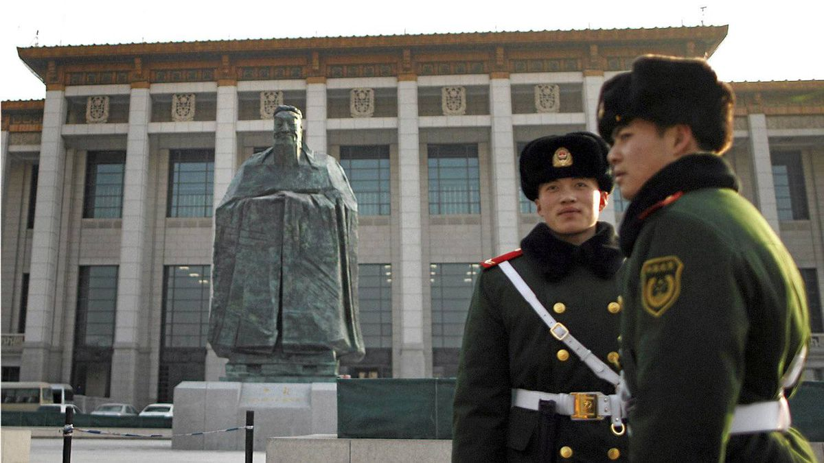 In this Wednesday, Jan. 12, 2011 photo, Chinese paramilitary policemen stands guard in front of a sculpture of the ancient philosopher Confucius on displayed in near the Tiananmen Square in Beijing, China's capital. The mammoth sculpture of Confucius was unveiled this week off one side of the giant plaza, the political heart of China. It's a curious juxtaposition for a site that's heavy with Communist history _ Mao's body is interred in the middle of it and his giant portrait hangs at one end.