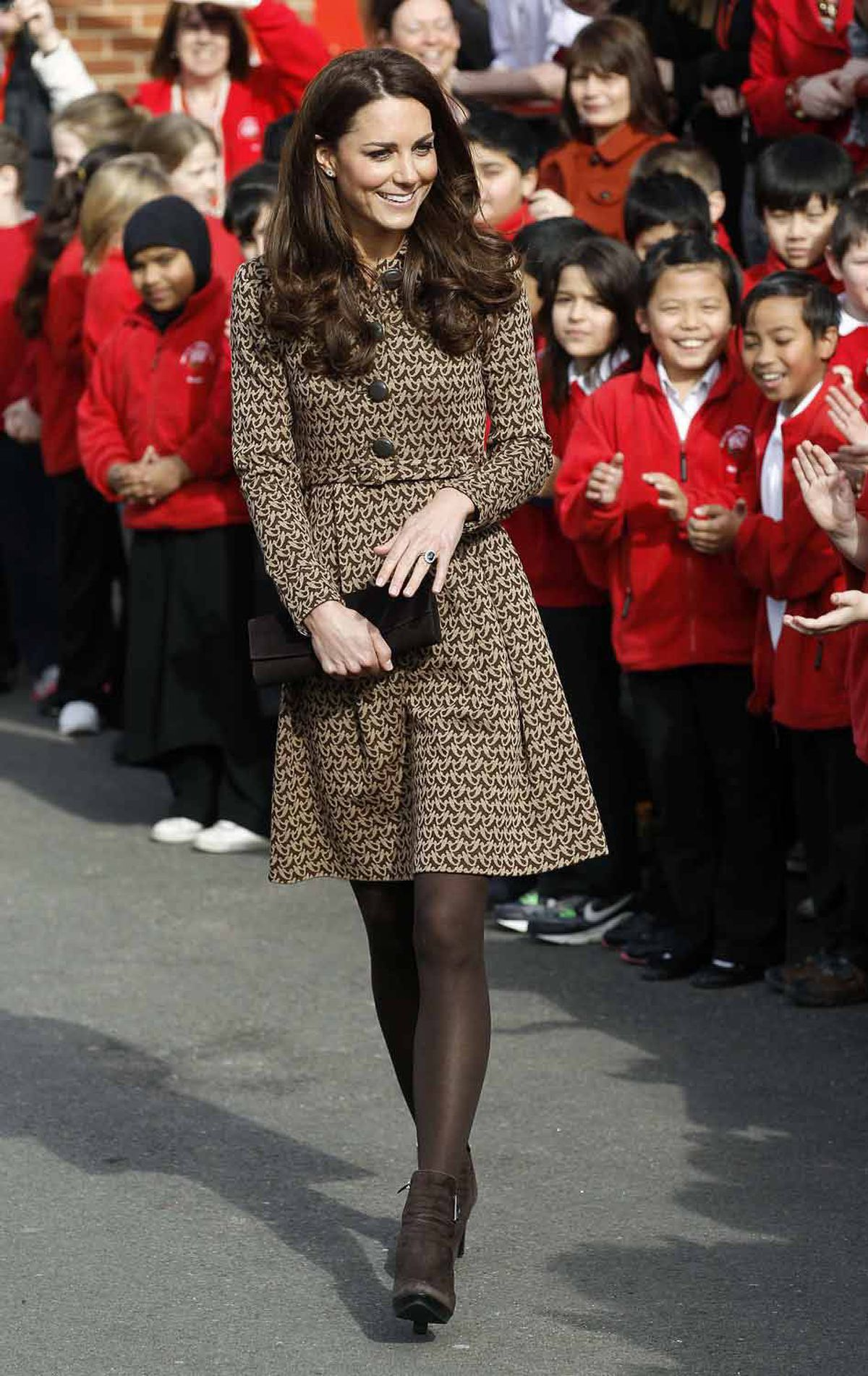 Kate looks prim and proper in a tweed coat-dress by Irish designer Orla Kiely as she visits Rose Hill Primary School in Oxford on February 21.