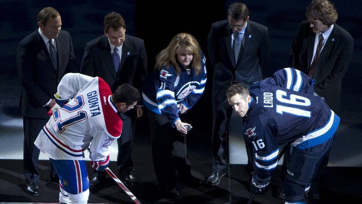 Shelly Rypien, mother of the late Winnipeg Jets' player Rick Rypien, drops the puck during the ceremonial face off with Winnipeg Jets captain Andrew Ladd (16) and Montreal Canadiens captain Brian Gionta (21) before the Jets inaugural game at the MTS Centre in Winnipeg, Sunday, Oct. 9, 2011. THE CANADIAN PRESS/Jonathan Hayward