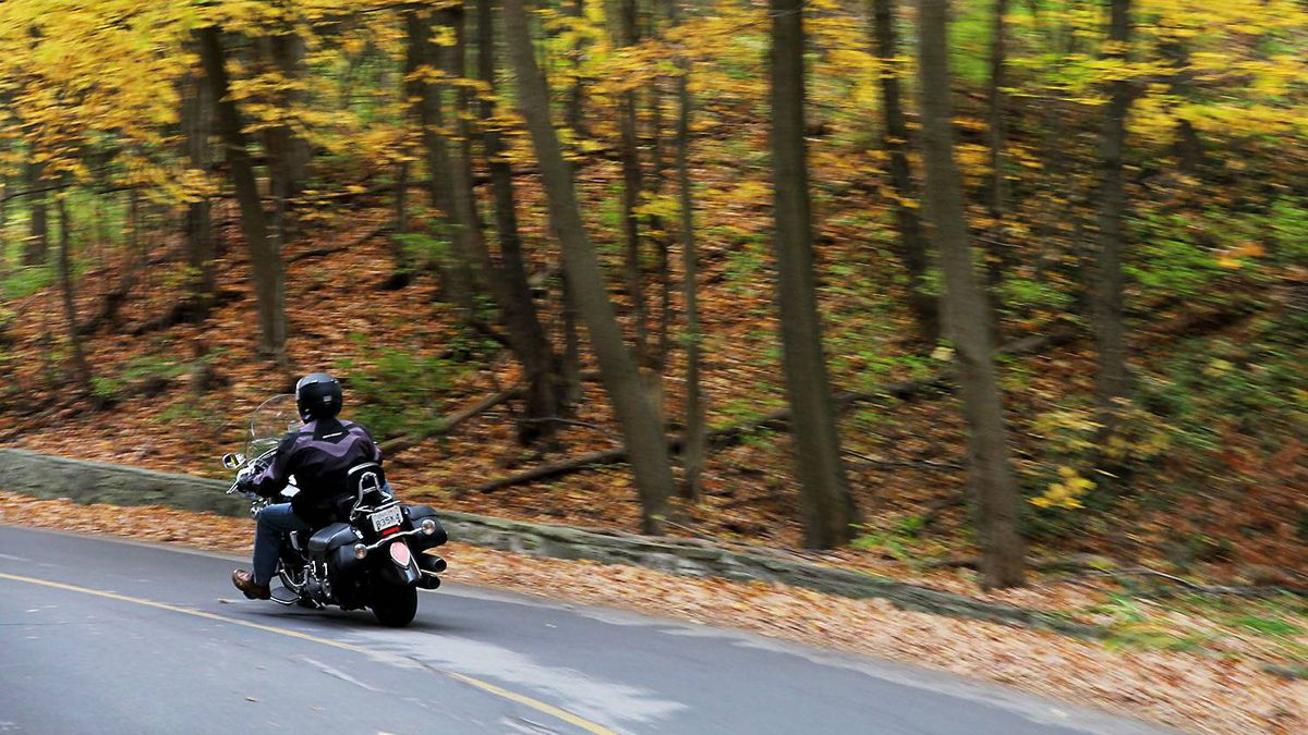 A motorcycle heads down through the curves that follow the Credit River through stone outcrops and deep hardwood forests