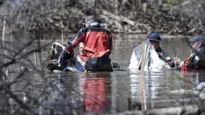 The RCMP underwater recovery team searches the wreckage of one of two plane involved in a mid-air collision, near St. Brieux,Sask. on Sunday March 13, 2012.