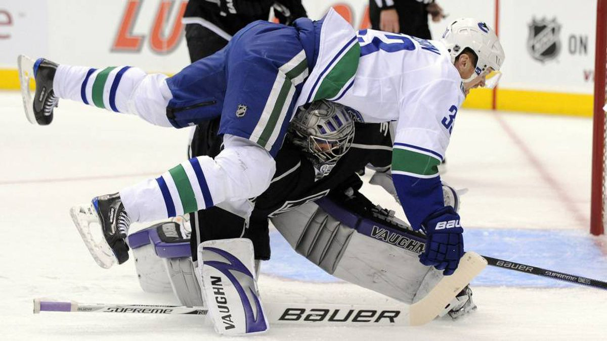 Vancouver Canucks center Henrik Sedin, top, of Sweden falls over Los Angeles Kings goalie Jonathan Quick during the first period in Game 3 of a first-round NHL hockey Western Conference playoff series, Monday, April 19, 2010, in Los Angeles. (