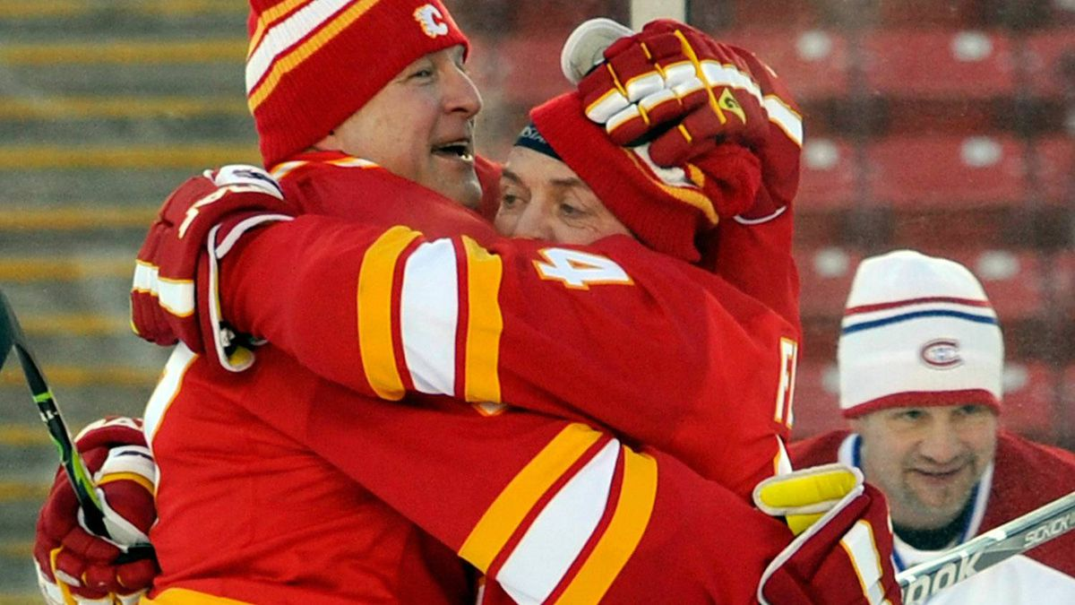 Brian MacLellan #27 (L) hugs Theo Fleury #14 (R) of the Calgary Flames Alumni following a goal against the Montreal Canadiens Alumni during the Alumni game held as part of the 2011 NHL Heritage Classic festivities at McMahon Stadium on February 19, 2011 in Calgary, Canada. (Photo by Dylan Lynch/Getty Images)
