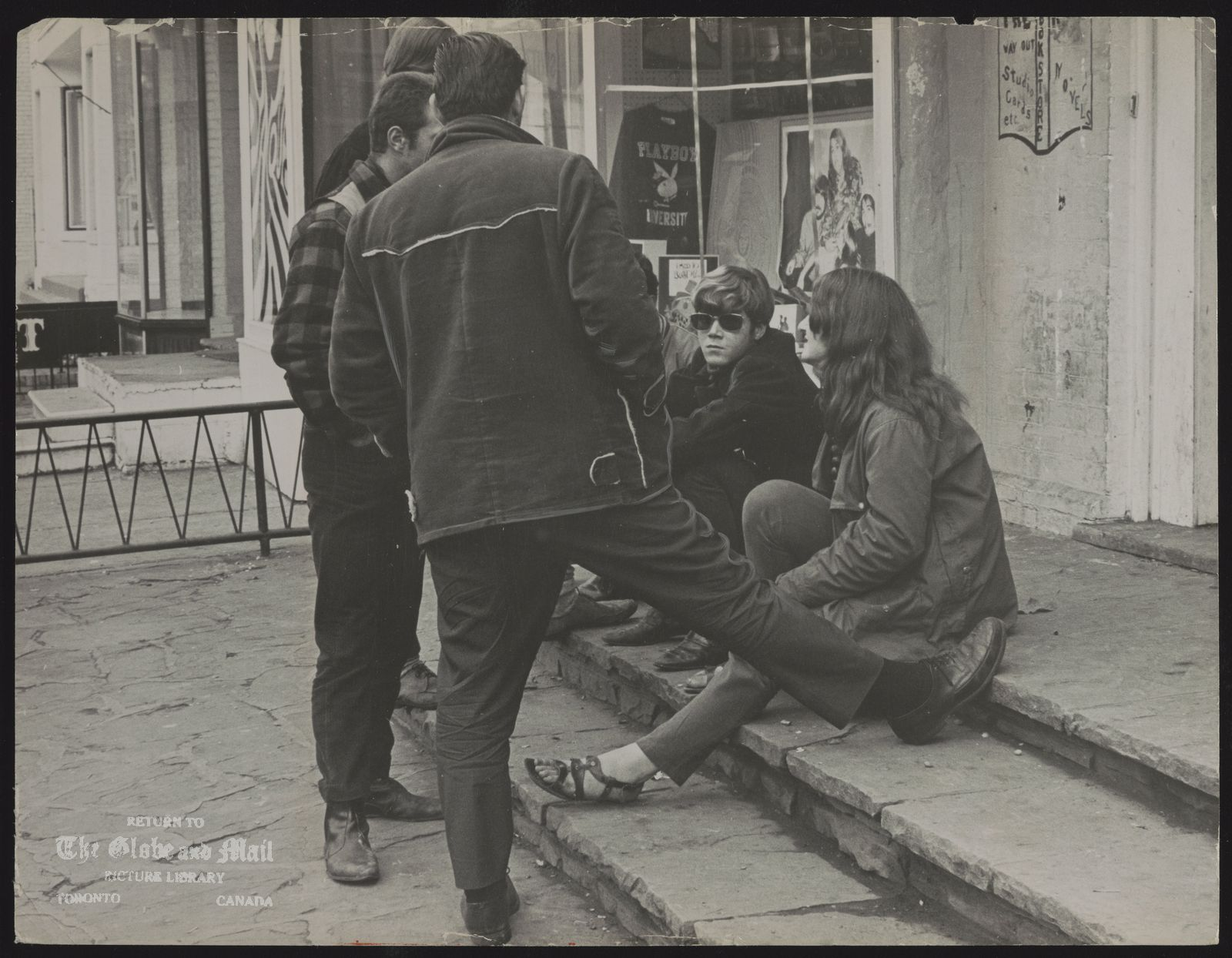 The notes transcribed from the back of this photograph are as follows: Hippies conversing in Yorkville yesterday. Girls in teens vanish in the village.