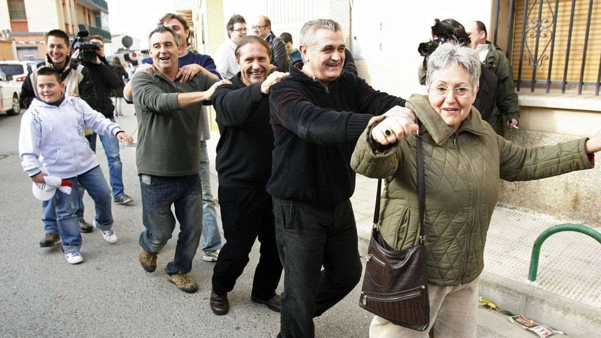 People in Granen, northern Spain, form a conga line Thursday to celebrate winning part of the 'El Gordo' lottery.