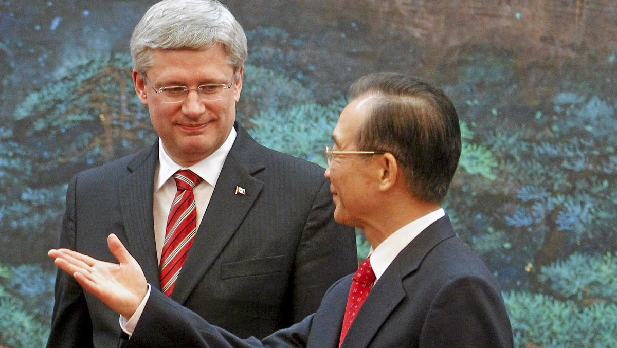 Canada's Prime Minister Stephen Harper looks on as Chinese Premier Wen Jiabao gestures after a signing ceremony at the Great Hall of the People in Beijing Feb. 8, 2012.