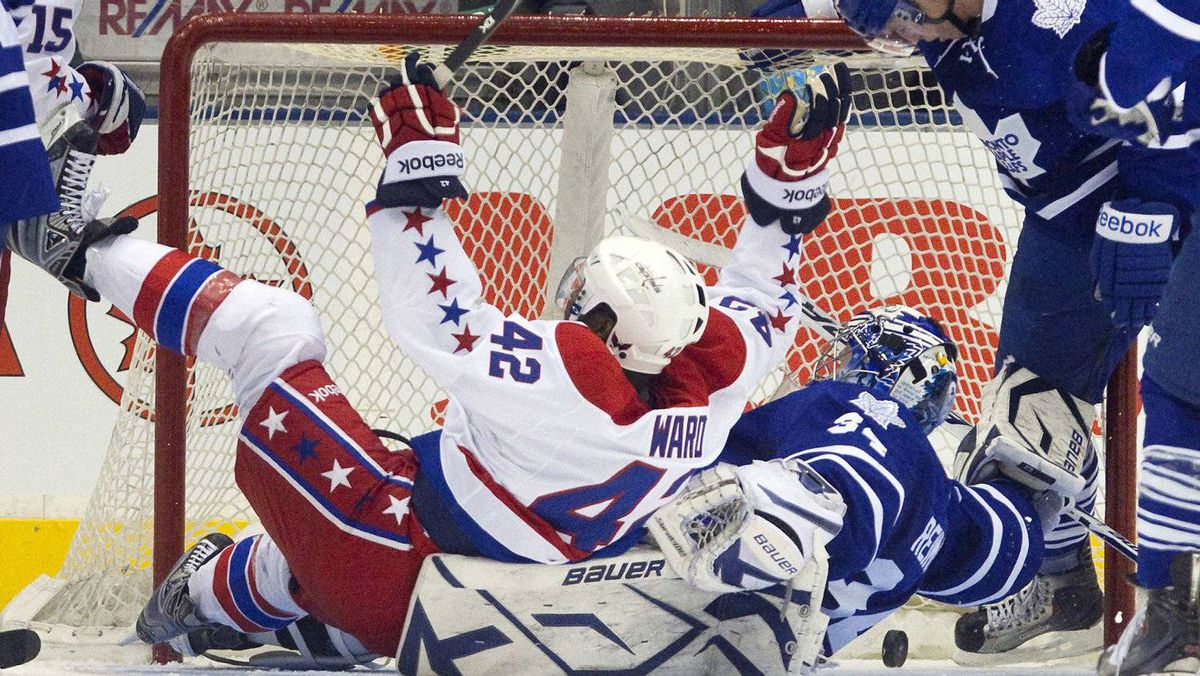 Toronto Maple Leafs goalie James Reimer looks over his shoulder at puck in the net off the stick of Washington Captials Jeff Halpern as Capitals Joel Ward (L) celebrates his assist on the Halpern goal in the second period of their NHL hockey game in Toronto February 25, 2012. The Caps won 4-2. REUTERS/Fred Thornhill