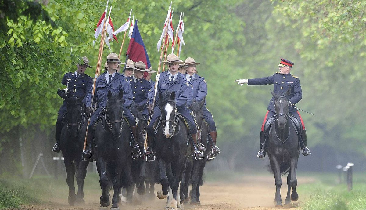 Captain Richard Chambers, right, riding master of the Household Cavalry, takes Royal Canadian Mounted Police for a training session in Hyde Park, London on May 22, 2012.
