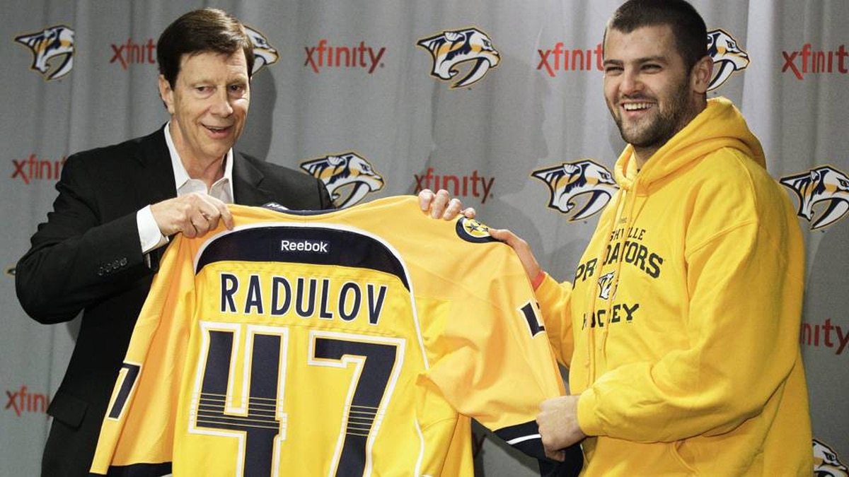 Nashville Predators forward Alexander Radulov, right, of Russia, poses with general manager David Poile, left, at a news conference on Wednesday.