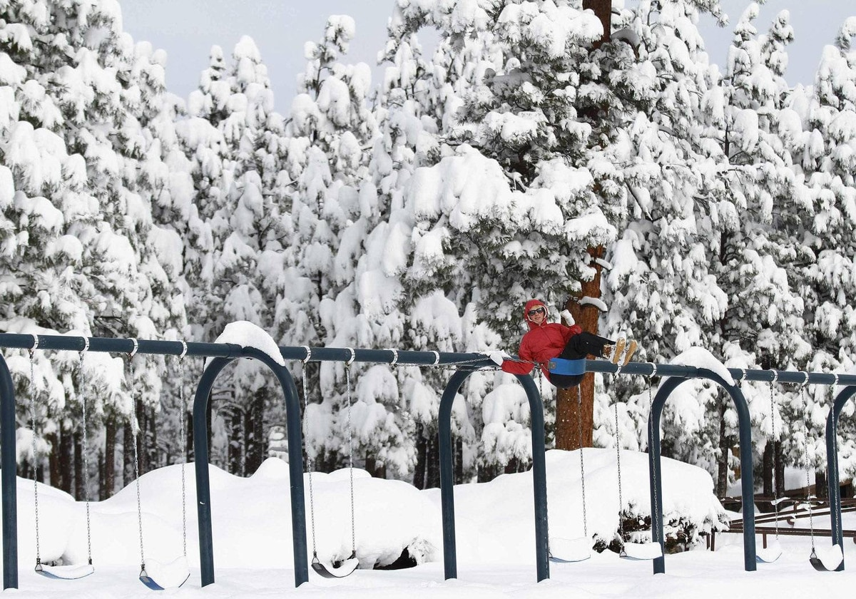 A woman sits on a swing set at Thorpe Park as several inches of snow cover the ground in Flagstaff, Arizona March 19, 2012.