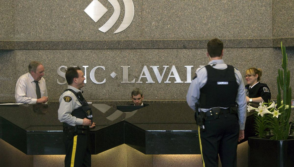 Royal Canadian Mounted Police (RCMP) officers stand in the headquarters of SNC Lavalin in Montreal April 13, 2012. Canada's Mounties were searching the Montreal headquarters of engineering giant SNC-Lavalin Group Inc on Friday following an internal company investigation that found a mysterious $56 million in improperly authorized payments.