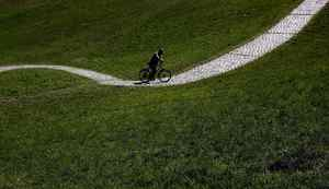 A cyclist makes his way through the Olympic park in Munich, Germany, Wednesday, April 25, 2012. Sunny weather is forecasted for Germany during the next few days. (AP Photo/Matthias Schrader)