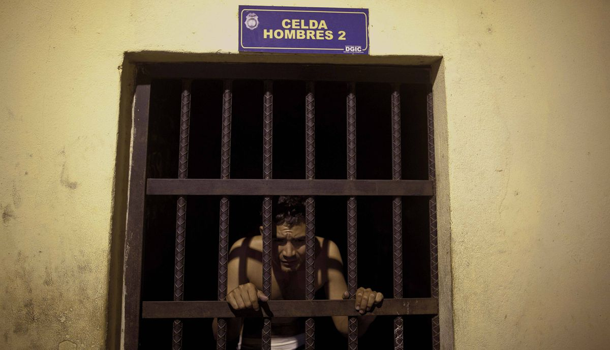 A detainee peers through the jail bars at a police station in San Pedro Sula, Honduras, MArch 8, 2012.