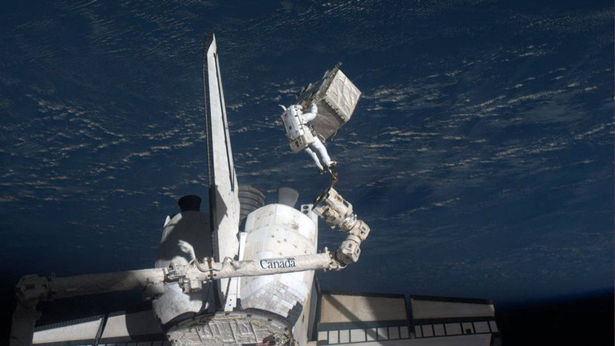 Spacewalker Ron Garan rides on the International Space Station's robotic arm with the Earth as a backdrop as he transfers a failed pump module to the cargo bay of space shuttle Atlantis during the final spacewalk, during a shuttle mission in this photo provided by NASA and taken July 12, 2011.