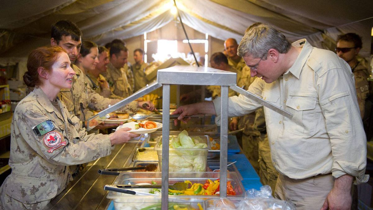 Prime Minister Stephen Harper, right, serves lunch to Cpt. Francesca Scorsone of Toronto as he visits a forward operating base in the district of Sperwan Ghar, Afghanistan on Monday, May 30, 2011.