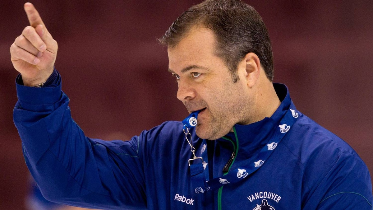 Vancouver Canucks' head coach Alain Vigneault directs his players through a drill during team practice in Vancouver. THE CANADIAN PRESS/Darryl Dyck