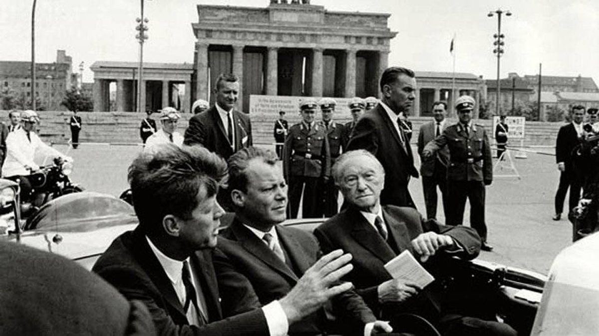 President John F. Kennedy, left, Willy Brandt, center, then mayor of West Berlin, and West German Chancellor Konrad Adenauer, right, ride in a car at the Brandenburg Gate on June 26, 1963.
