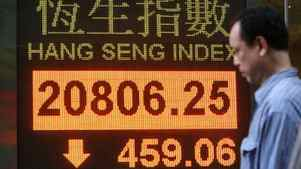 A man walks past a screen showing the Hong Kong's Hang Seng index which lost 2.16 percent to 20,806.25 outside a bank in Hong Kong Tuesday, March 6, 2012.