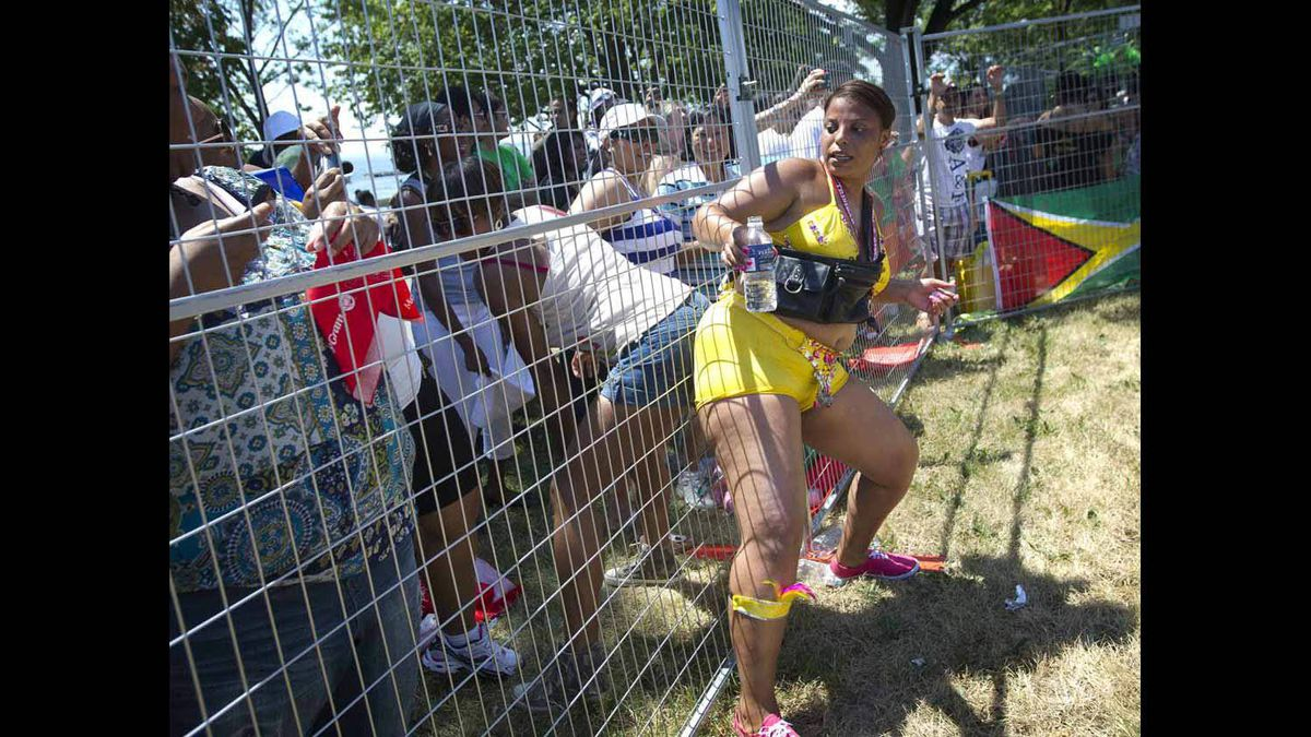A dancer and spectator don't let fences get in the way of a Caribbean Carnival celebration.