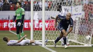 Sporting KC's Aurelien Collin (R) reacts after scoring against the Vancouver Whitecaps goalkeeper Joe Cannon (C) during the first half of their MLS soccer game in Vancouver, British Columbia April 18, 2012.