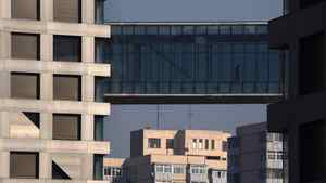 A man walks across a pedestrian bridge joining two residential apartment buildings in central Beijing January 12, 2012.