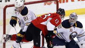 Buffalo Sabres' goalie Ryan Miller (R) watches the puck as Brayden McNabb (L) collides with Ottawa Senators' Peter Regin during the third period of their NHL hockey game in Ottawa December 20, 2011. REUTERS/Blair Gable