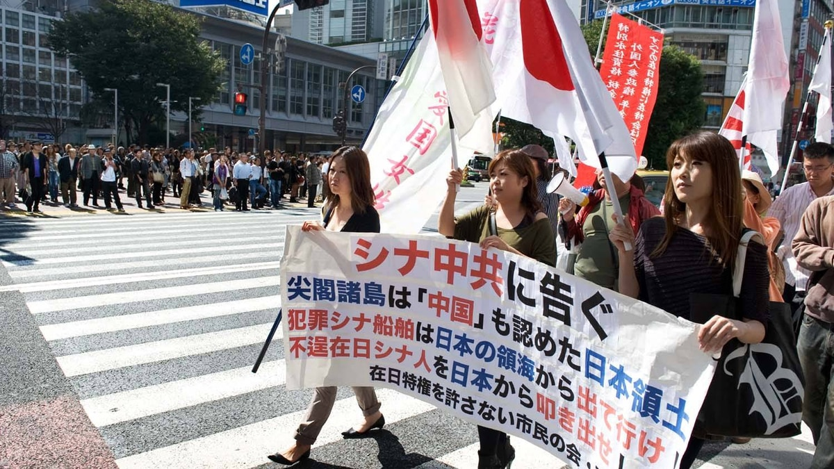 """Japanese right-wing demonstration in central Tokyo on October 3, 2010. Roughly translated, the sign says: """"China already accepted that the Senkaku Islands are Japanese territory. Illegal ships should get out. Recalcitrant Chinese should get out."""""""