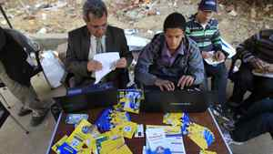 Muslim Brotherhood members help voters find their registration numbers before voting outside a polling station in the Manial neighbourhood of Cairo on Nov. 28, 2011.