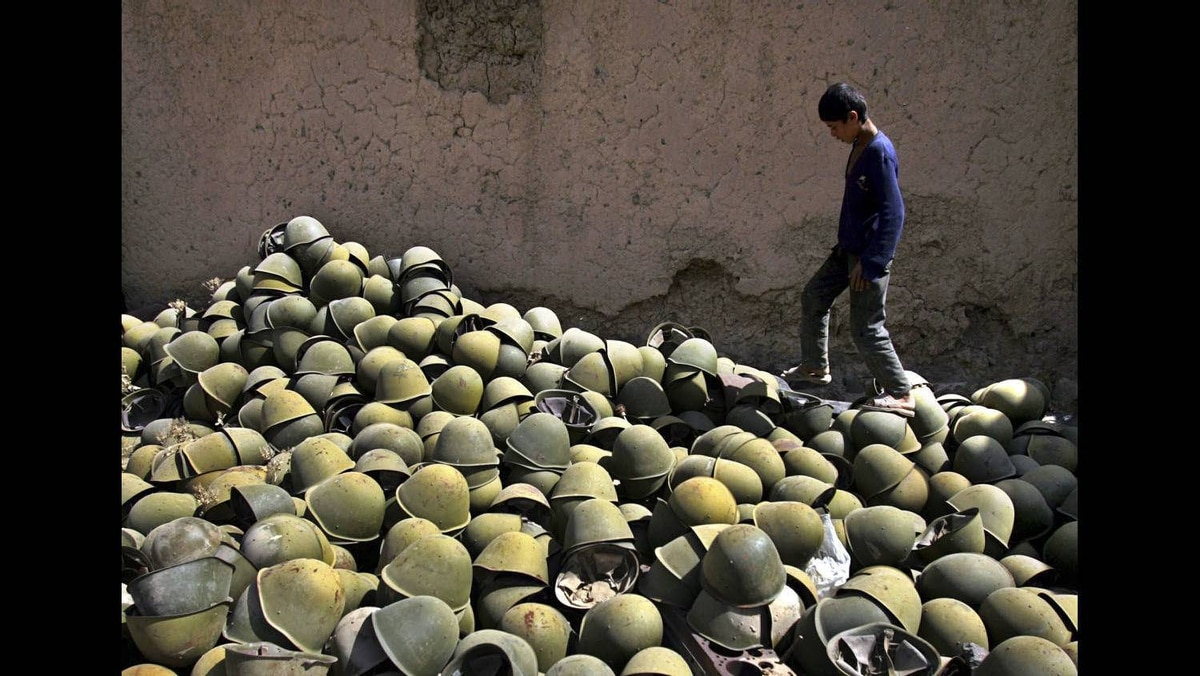 Afghan boy walks next to a pile of Russian-made helmets in the Panjshir Valley, some 100km north of Kabul, August 10, 2005.