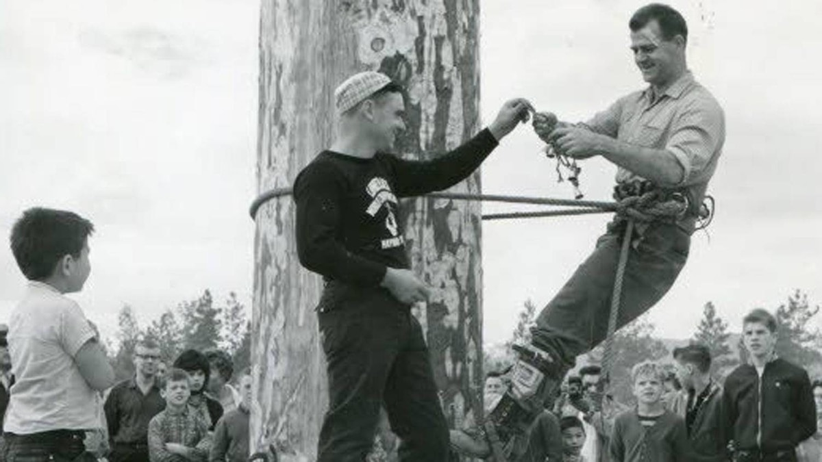 Frank Howard (right) prepares to climb a 90-foot spar as part of loggers' sports days in Terrace, B.C.