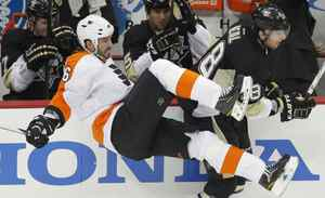 Pittsburgh Penguins' James Neal (18) knocks Philadelphia Flyers' Andreas Lilja (6) to the ice in the second period of Game 1 of their NHL Eastern Conference quarter-final hockey game in Pittsburgh, Pennsylvania, April 11, 2012.