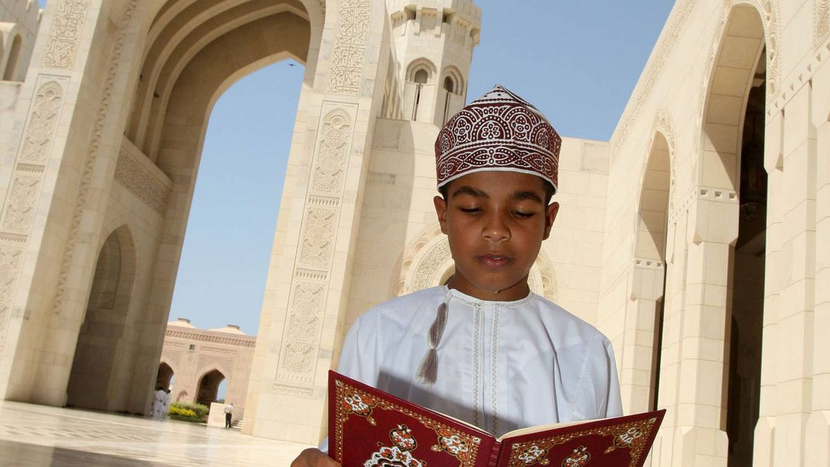 An Omani boy reads the Koran in the courtyard of Muscat's Grand Mosque before the noon prayer on the first Friday of the holy month of Ramadan in the Gulf sultanate of Oman on September 5, 2008.