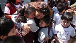 A woman comforts her children outside a school at the Roma neighborhood after a earthquake was felt in Mexico City on March 20, 2012.