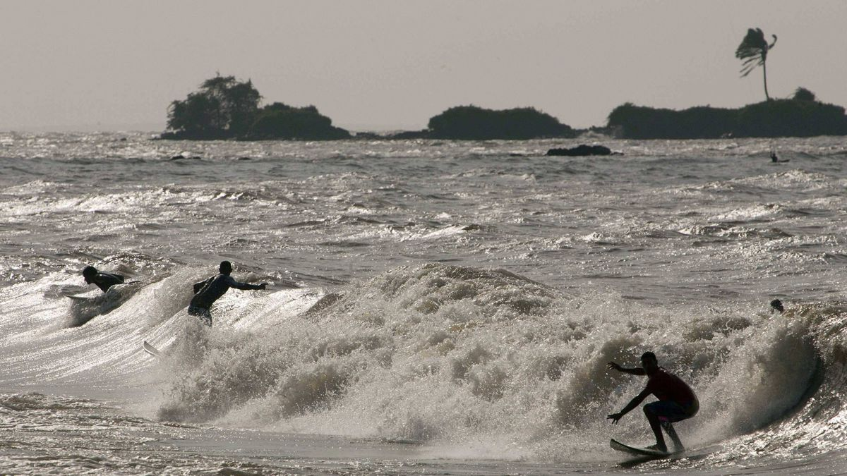 Surfers ride the waves in Marajo Bay near the mouth of the Amazon River in Brazil.