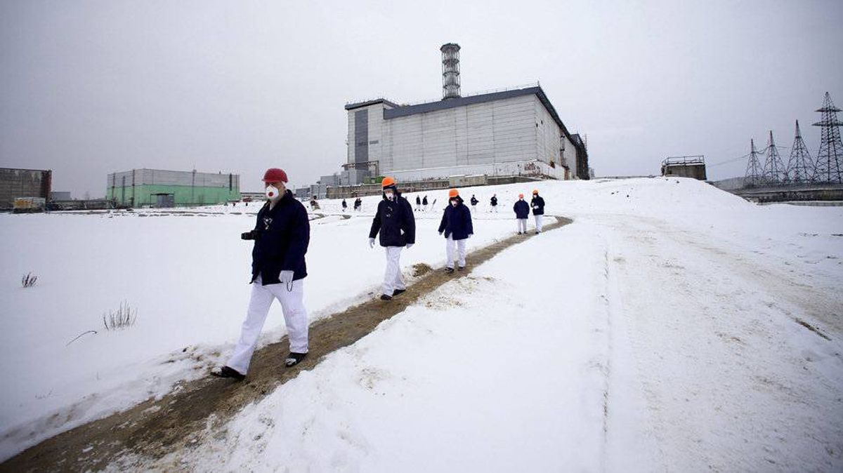 Visitors walk in protective clothing on the grounds of the Chernobyl nuclear power plant in Ukraine.