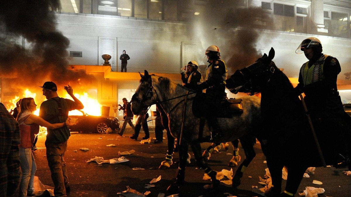 Police on horseback ride through the street past a fire on June 15, 2011 in Vancouver.