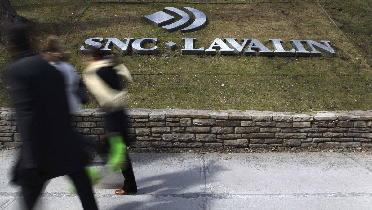 Pedestrians walk past a sign for the head office of SNC Lavalin in downtown Montreal March 26, 2012.