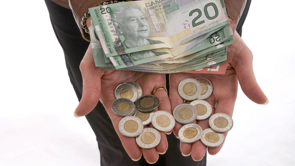 Hands stretched out and holding a stack of Canadian $20 and $2 coins.